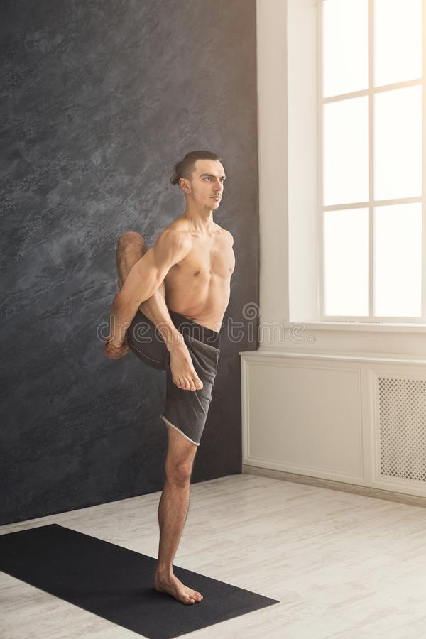 Young flexible man standing on hands stock images