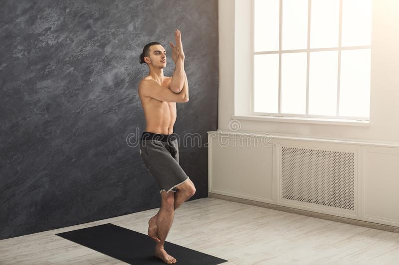 Young flexible man practicing yoga at gym royalty free stock photos