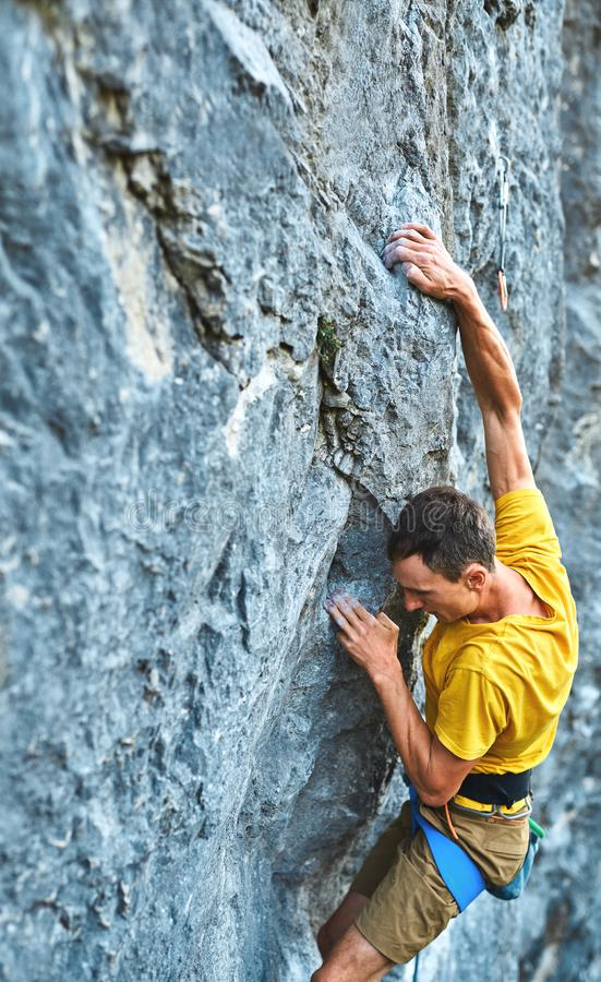 Young strong man rock climber in yellow t-shirt, climbing on a cliff. Young strong man rock climber climbing on a high vertical limestone cliff, reaching holds royalty free stock photo