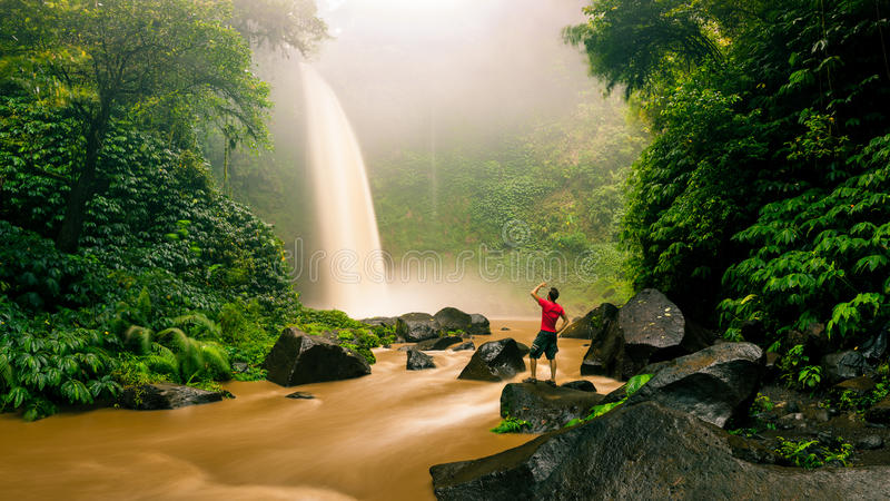 Young strong man traveler enjoy spectacular morning view, beautiful Nungnung Waterfall royalty free stock photo