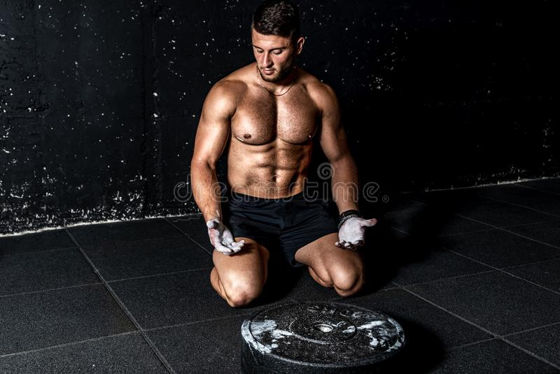Young strong muscular man with big muscles sitting on the gym floor after heavy workout training with barbell weight plate.  stock photography