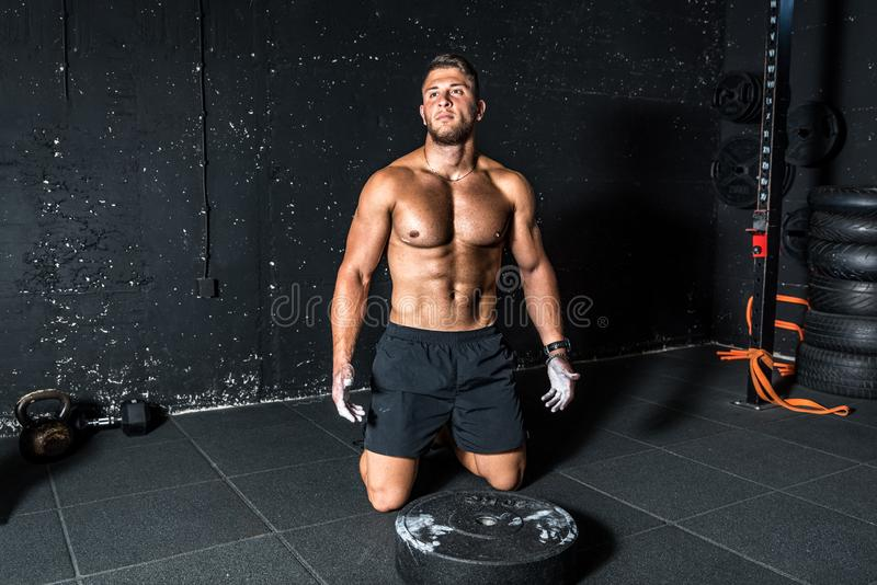 Young strong muscular man with big muscles sitting on the gym floor after heavy workout training with barbell weight plate.  royalty free stock images