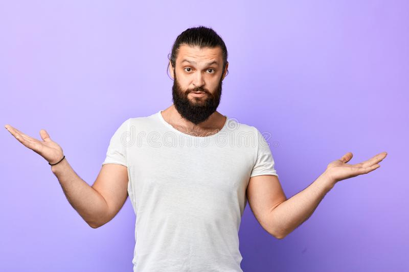 Young strong muscular man showing ignorance, shrugging shoulder stock image