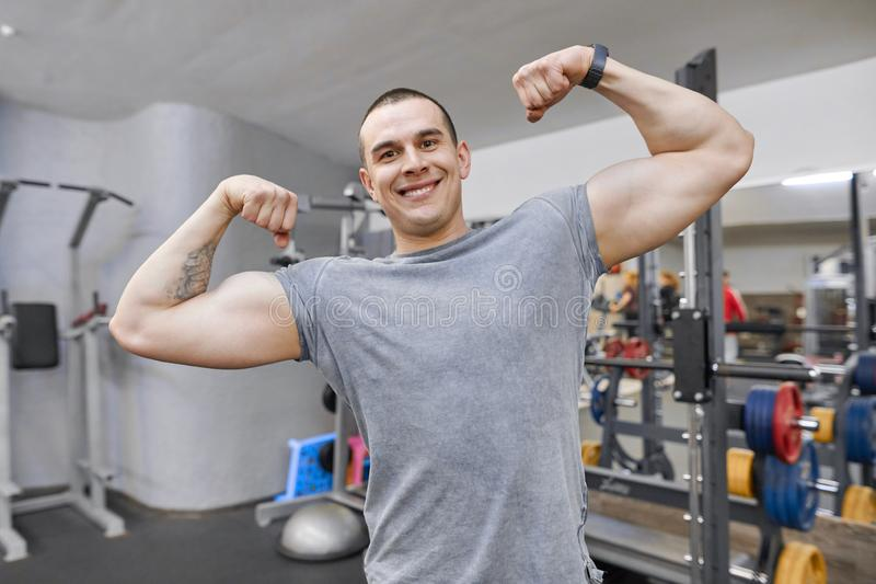 Young strong smiling muscular man in gym showing strong muscular arms royalty free stock image