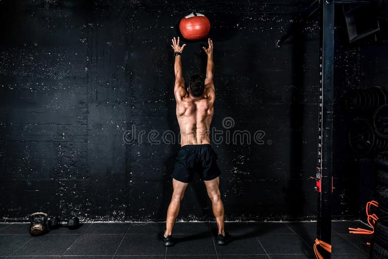 Young strong sweaty focused fit muscular man with big muscles doing throwing medicine ball up on the wall for training hard core w. Med ball throw, Young strong royalty free stock photography