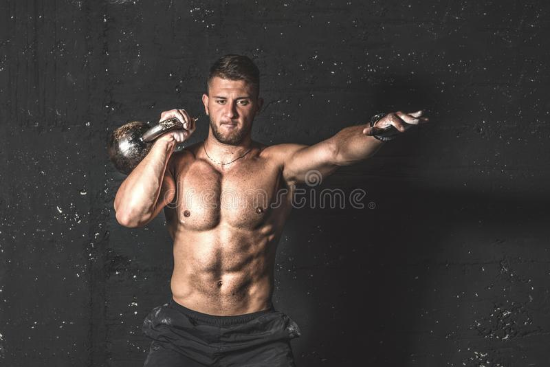 Young strong sweaty focused fit muscular man with big muscles holding heavy kettle bell for training hard core workout in the gym stock images