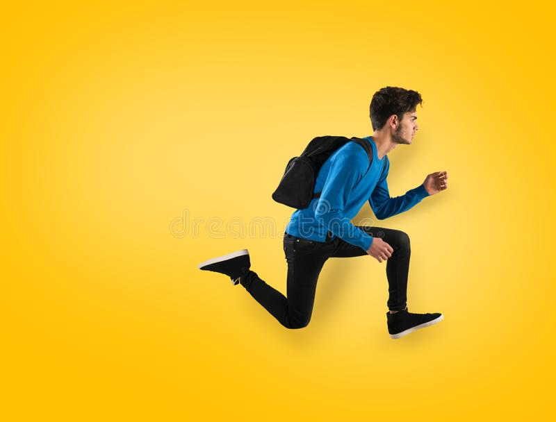 Young student fast run on yellow background stock photos