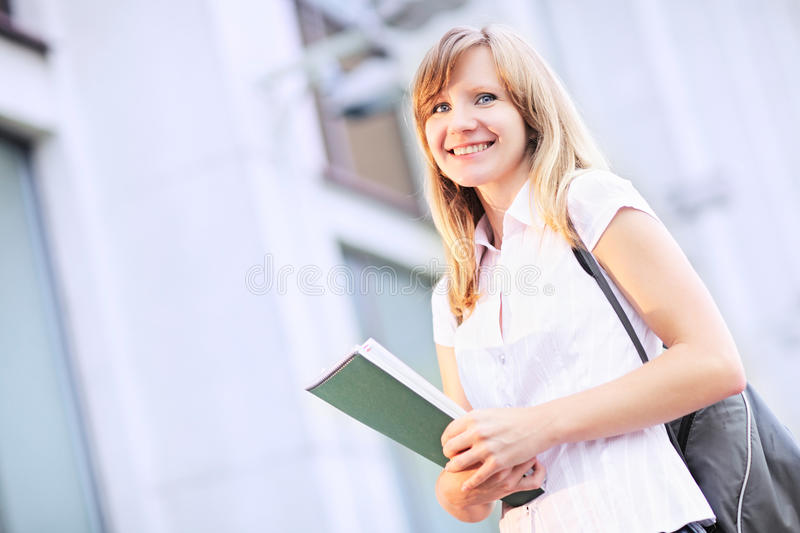 Young student, beautiful caucasian woman standing on blurred university building background in the morning. stock photos