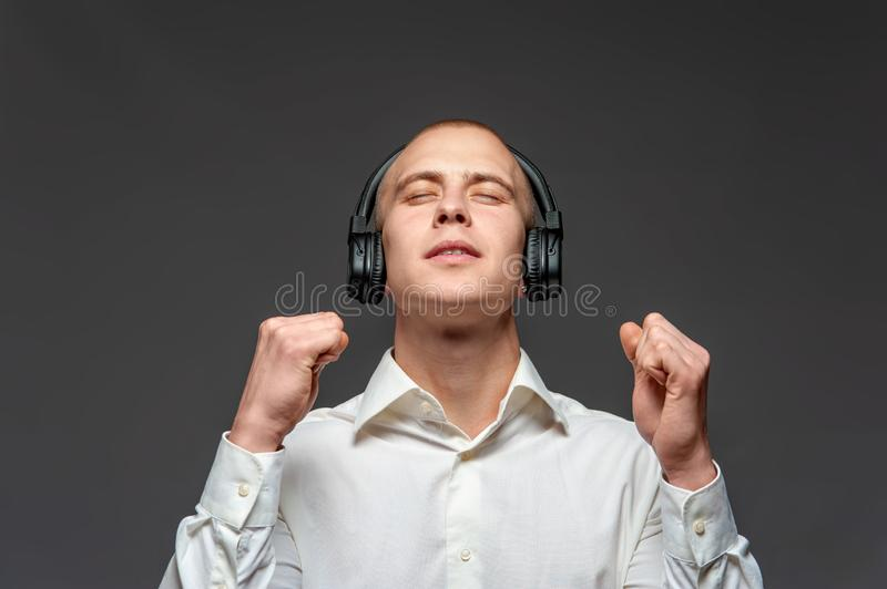 Young student boy listens to a song. Of his favorite band in headphones waiting for their imminent concert pose on a black background. Concept of online music royalty free stock photography