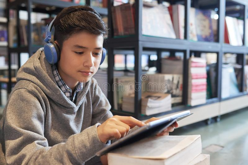 School boy in headphones in library with tablet royalty free stock photos