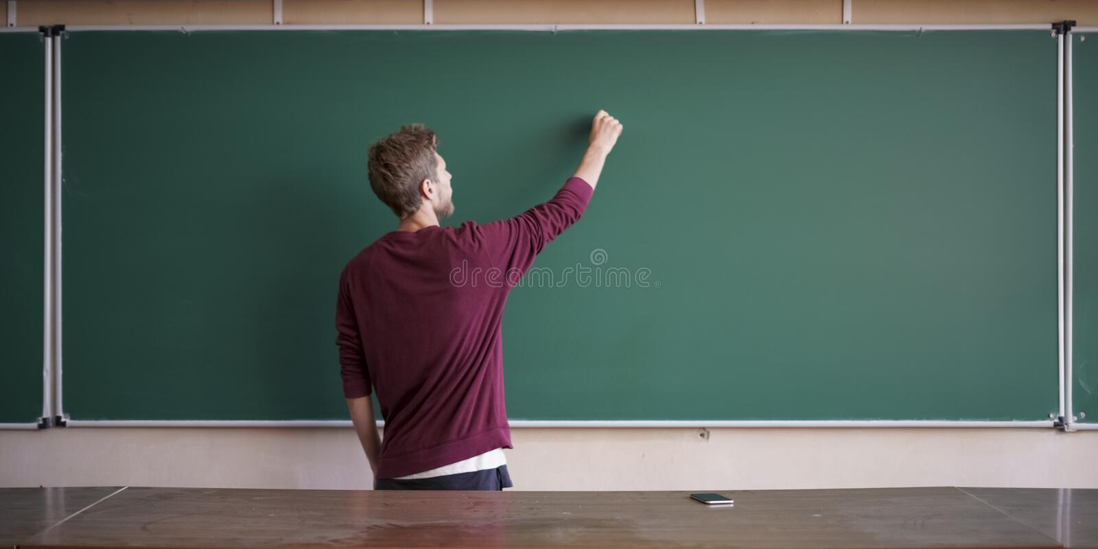 Young student in casual writing physics formula on empty blank blackboard during study course copy space mock up royalty free stock image