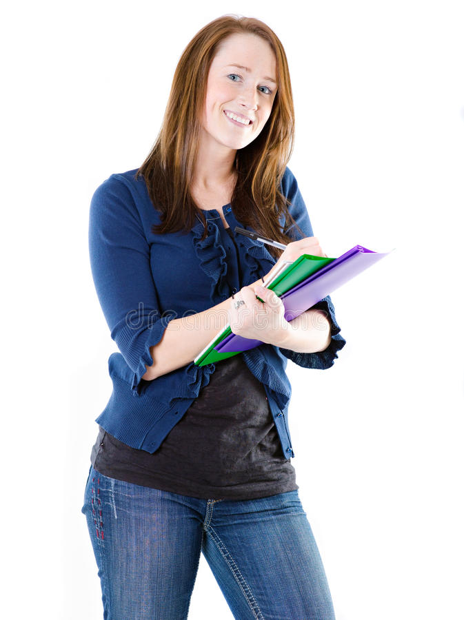 Young student with folders. Closeup of smiling young female student with pen and folders, isolated on white background stock photography