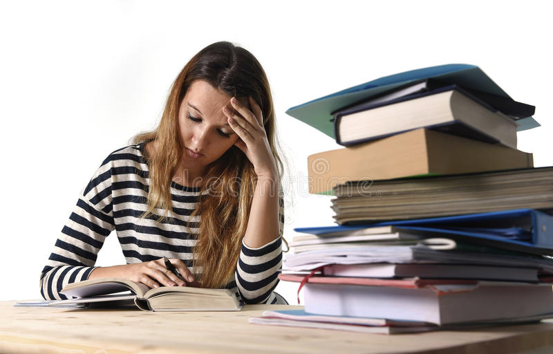 Young student girl concentrated studying for exam at college library education concept. Young student girl concentrated studying with textbook at college library royalty free stock images
