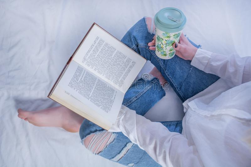 Young student girl reading book in cozy bed and holding book on legs with bare feet and drinking hot coffee in retro cup stock images