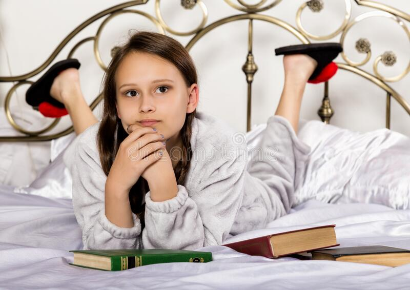Young student girl reads a book while lying on a bed doing homework stock photos