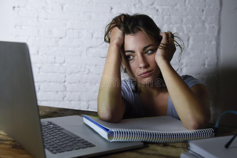 Young student girl studying tired at home laptop computer preparing exam exhausted and frustrated feeling stress royalty free stock image