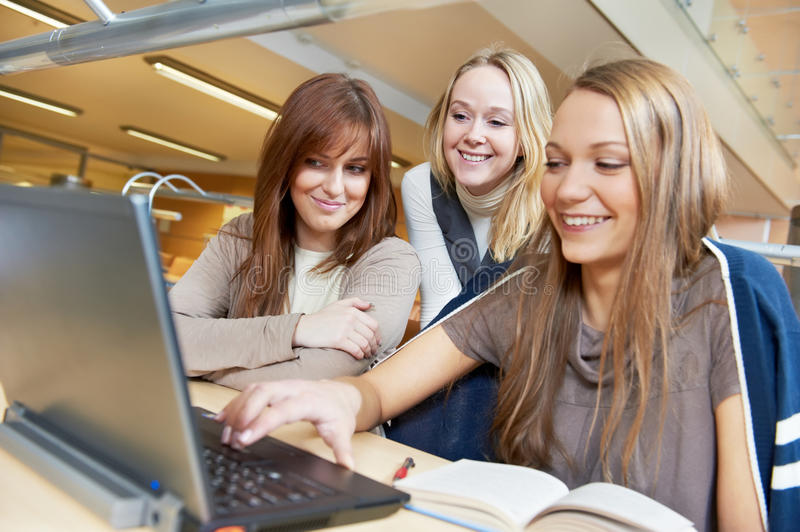 Young student girls working with laptop in library royalty free stock image