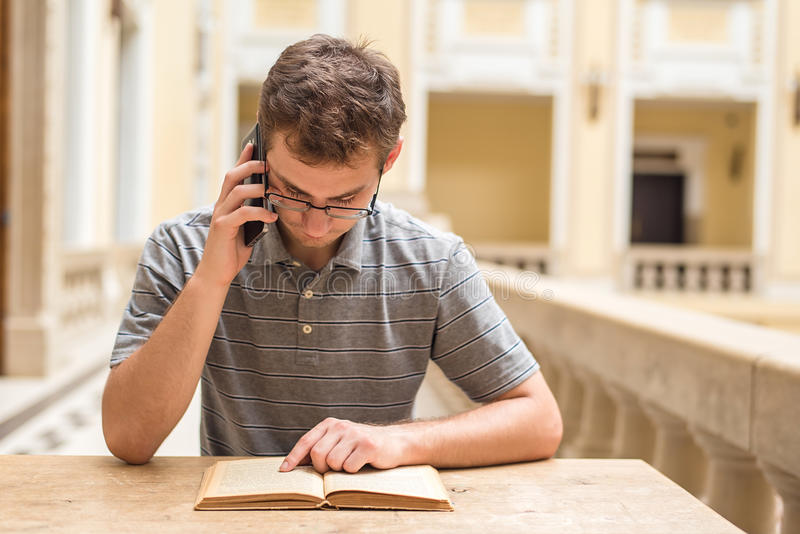 Young student guy learning and use his phone royalty free stock image