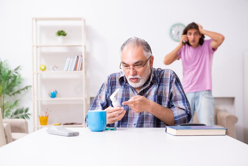 Young student and his old grandpa at home. The young student and his old grandpa at home stock image