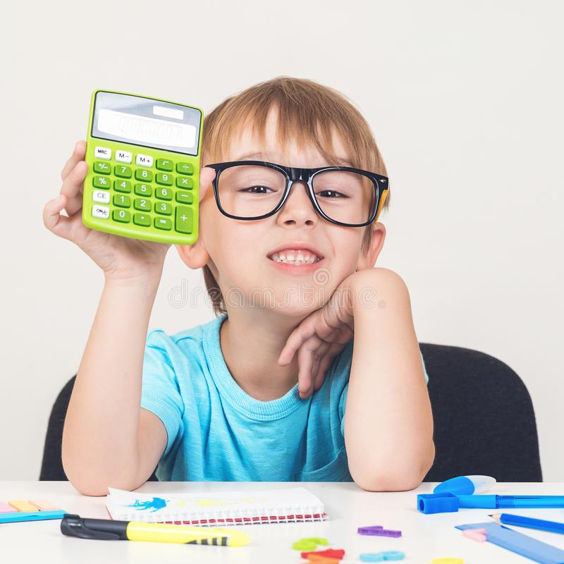 Young student holding calculator. Little boy in glasses sitting at desk. Education and development. Back to school concept. stock photo