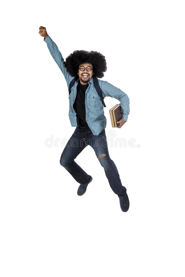 Young student jumping with book in hand stock photo