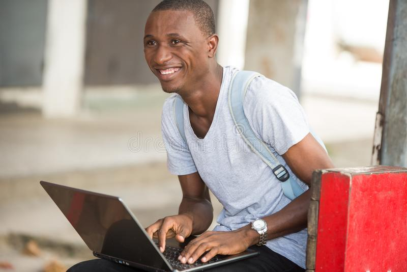 Young student man sitting in city working with laptop. Young attractive student man in the city working with laptop looking for satisfaction and confidence in royalty free stock photo