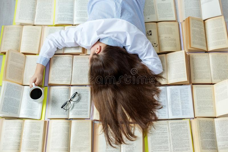 A young student is preparing for exams. A lot of books. Concept for World Book Day, lifestyle, study, education stock photo