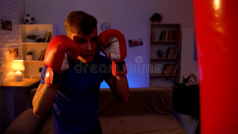 Young student punching boxing bag, releasing negative emotions, reducing stress royalty free stock photography