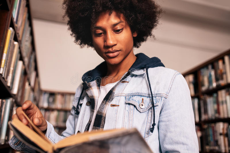 Young student reading a book in library royalty free stock image