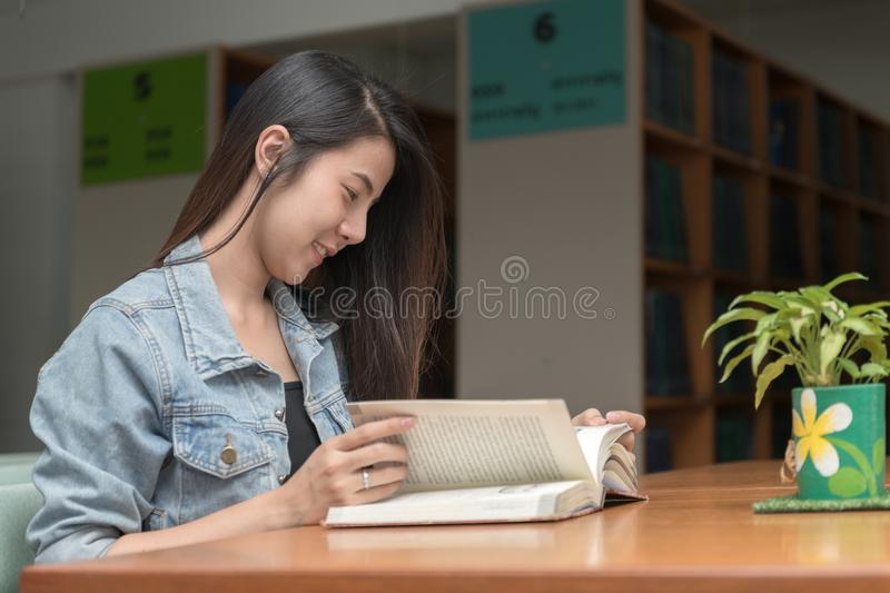 Young student reading book it in university library stock photography