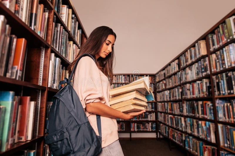 Young student reading books in library royalty free stock images