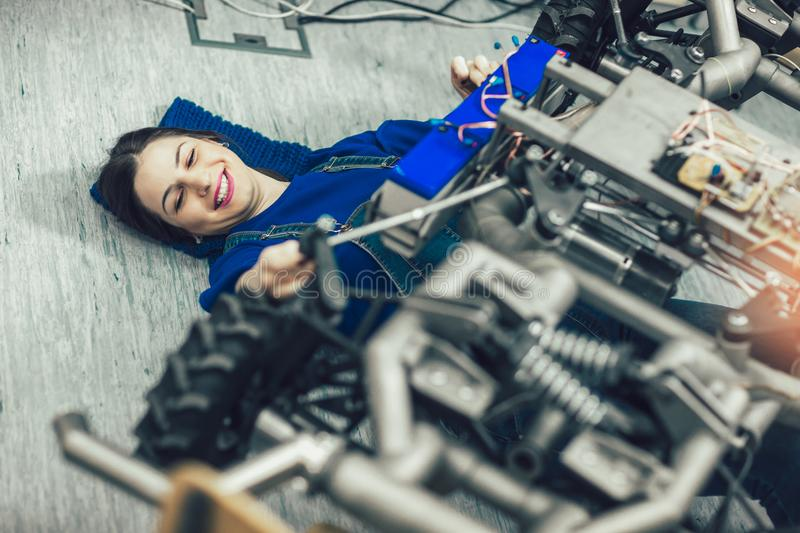 Young student of robotics preparing car robot for testing royalty free stock photos