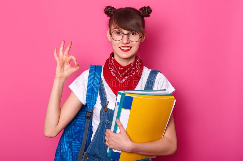 Young student showing okay sign, has good result of exam. Schoolgirl stands isolated over pink background. Happy girl studies at royalty free stock photo