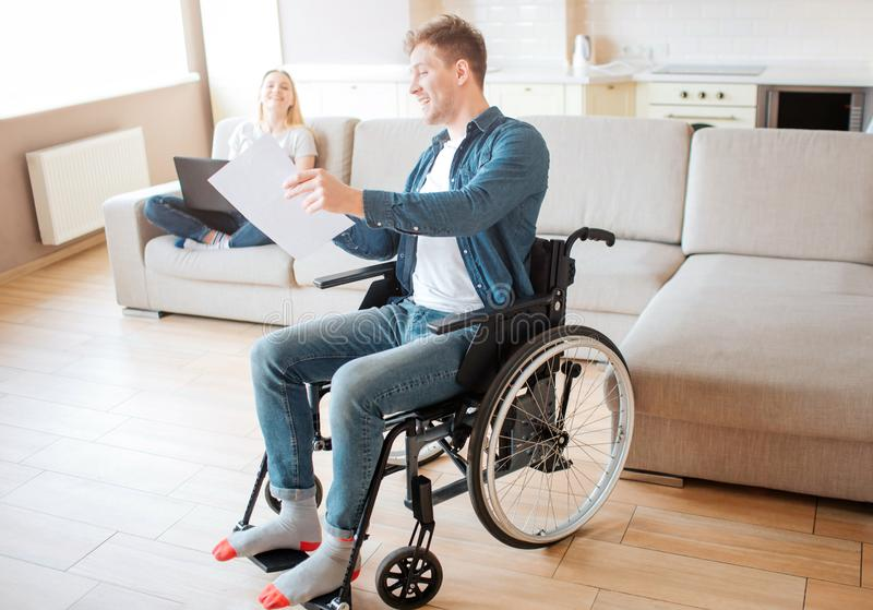 Young student with special needs and disability. Sit on wheelchair. Showing piece of paper to woman. They smile and look royalty free stock images