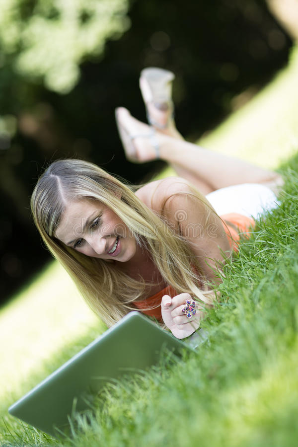 Young student surfing the internet in a park royalty free stock images