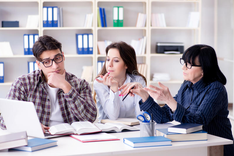 The young student and teacher during tutoring lesson royalty free stock photo