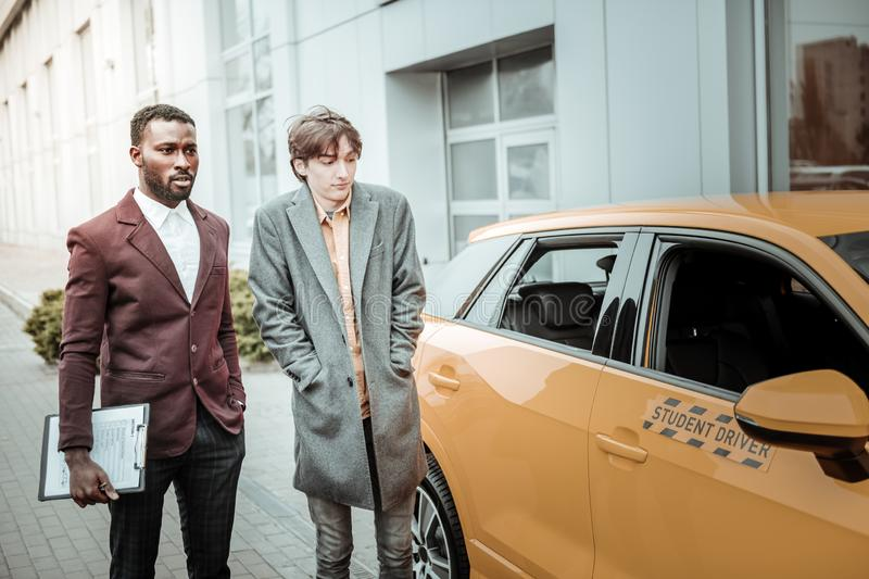 Young student wearing grey coat standing near his student driver car royalty free stock images