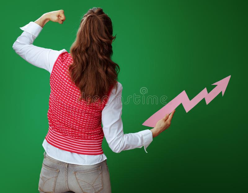 Young student woman with rising graphics arrow showing biceps. Seen from behind young student woman in grey jeans and pink sleeveless shirt with a rising stock images