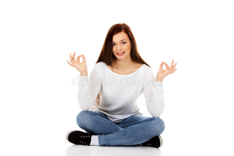 Young student woman sitting and doing yoga stock images