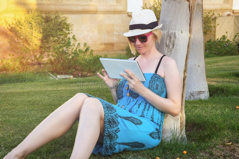 Young student woman sitting on a green grass in a park and holding a tablet computer royalty free stock photography
