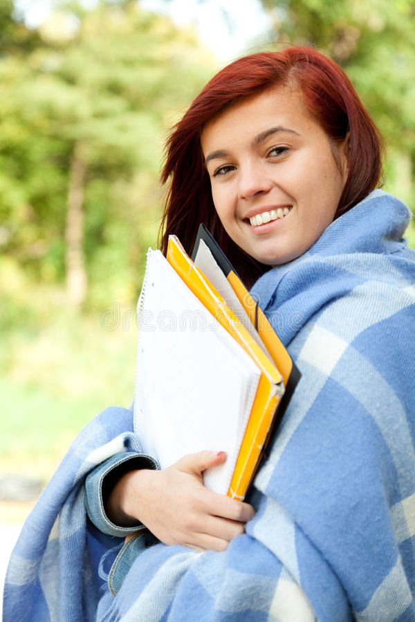 Young student woman wrapped in blanket, outdoors