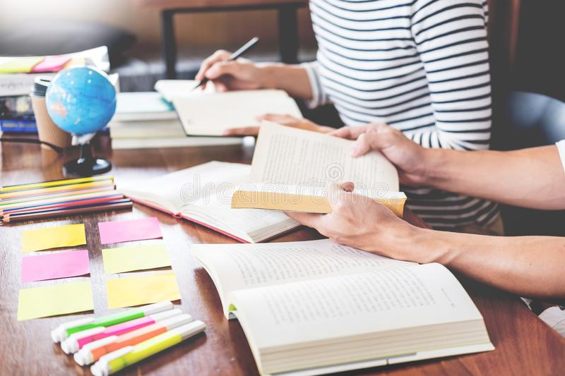 Young students classmates help friend catching up workbook and learning tutoring in a library, education and school concept. Young students classmates help royalty free stock photography