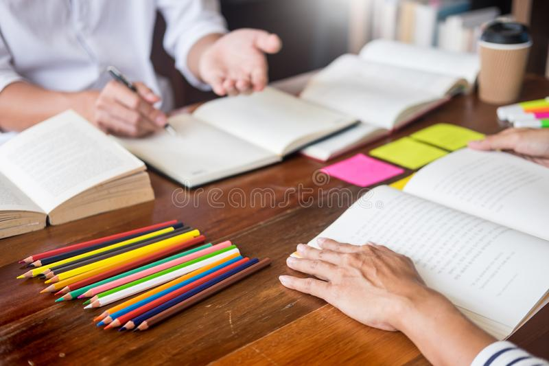 Young students classmates help friend catching up workbook and learning tutoring in a library, education and school concept. Young students classmates help stock images