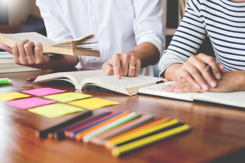 Young students classmates help friend catching up workbook and learning tutoring in a library, education and school concept. Young students classmates help royalty free stock images