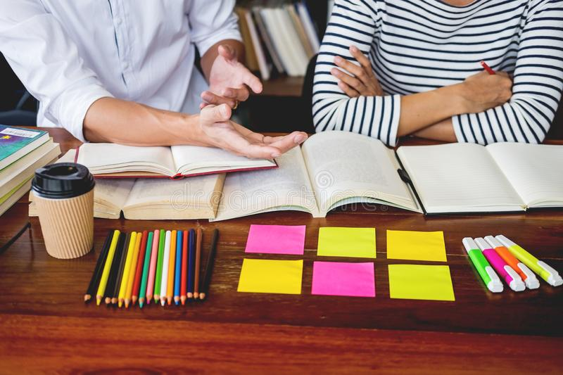 Young students classmates help friend catching up workbook and learning tutoring in a library, education and school concept.  stock images