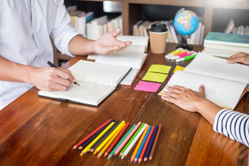 Young students classmates help friend catching up workbook and learning tutoring in a library, education and school concept.  stock photography