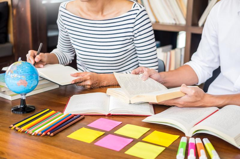 Young students classmates help friend catching up workbook and learning tutoring in a library, education and school concept.  stock photo