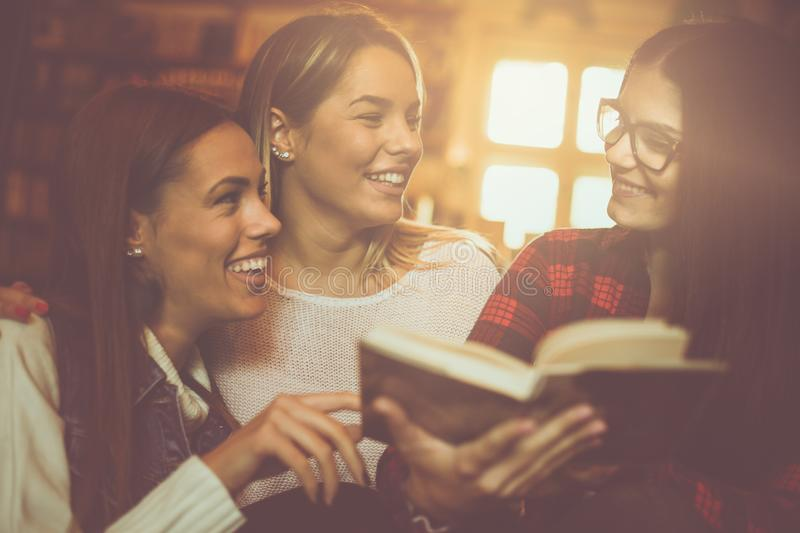 Students girls in library reading book and having conversa royalty free stock photography