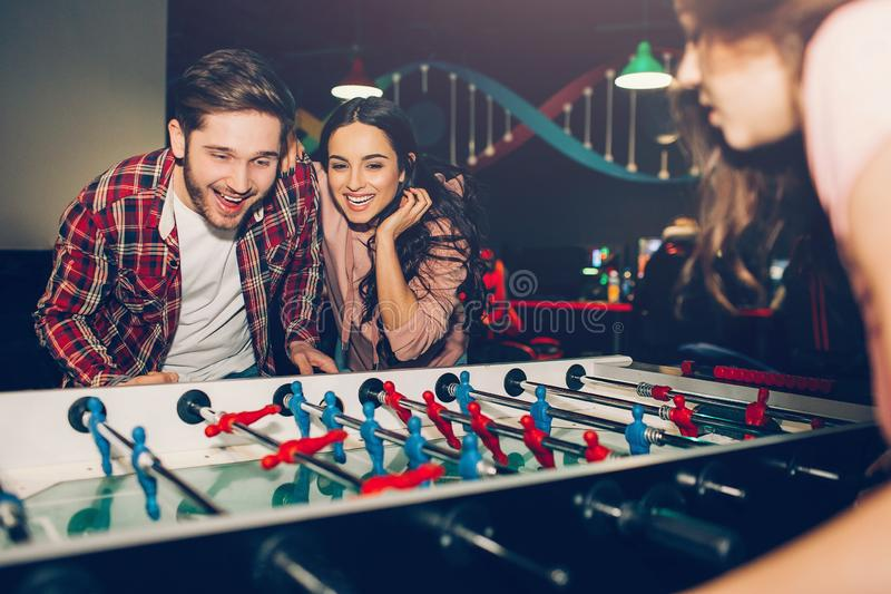 Young students playing table soccer together in room. Man opponent to woman. They excited and playful. royalty free stock image