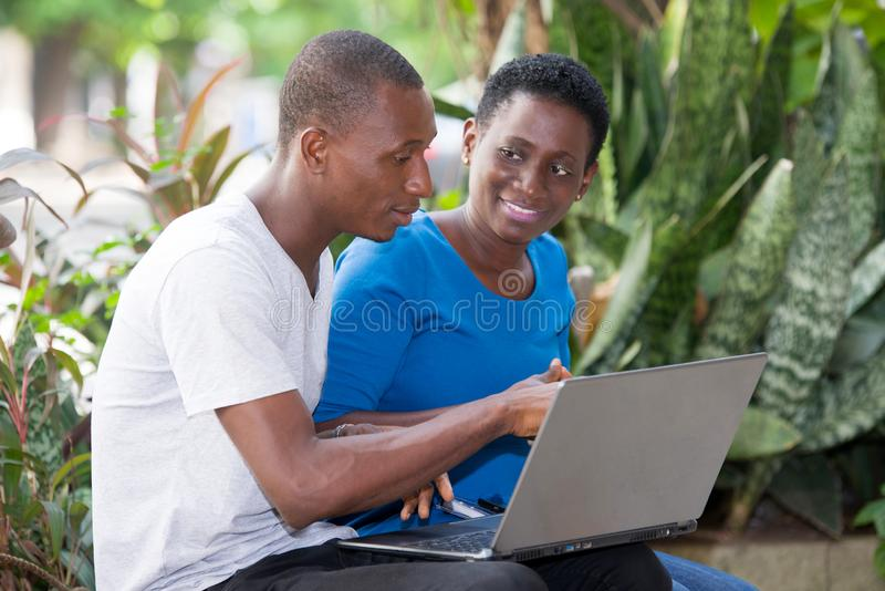 Portrait of young students with laptop. Young students sitting in park doing research looking at laptop while smiling stock photos